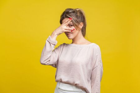 Portrait of curious beautiful young woman with fair hair in casual beige blouse standing, peeking through fingers with suspicious and prying eyes. indoor studio shot isolated on yellow background