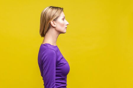 Side view of beautiful serious woman in elegant purple dress showing her neck with clean young skin, beauty skincare concept, copy space on right side. indoor studio shot isolated on yellow background