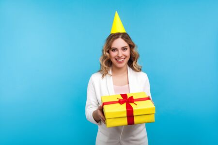 Portrait of attractive positive woman with birthday party cone on head and in white jacket holding present box and smiling at camera, greeting on holiday. studio shot isolated on blue background