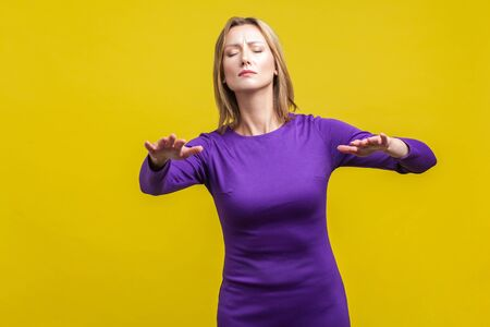 Portrait of blind disoriented young woman in elegant tight purple dress walking with closed eyes, reaching out hands to find lost way, vision loss. indoor studio shot isolated on yellow background