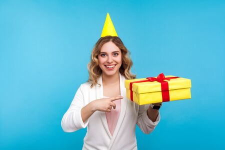 Portrait of excited positive woman with birthday party cone on head and in white jacket pointing at present box and smiling at camera, greeting on holiday. studio shot isolated on blue background