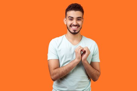 Portrait of joyous handsome brunette man in love making heart gesture with hands and smiling broadly at camera, demonstrating romantic feelings. indoor studio shot isolated on orange background Фото со стока