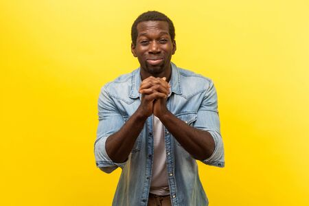 Portrait of hopeless depressed young man in denim casual shirt holding hands in prayer, pleading asking heartily, looking with guilty expression. indoor studio shot isolated on yellow background