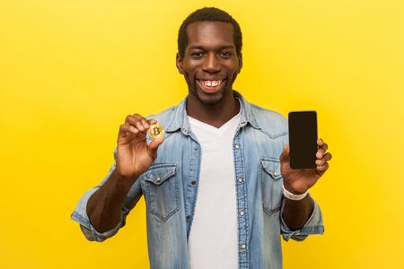 Cryptocurrency mobile application. Portrait of excited joyous man in denim casual shirt holding cellphone and golden bitcoin, smiling at camera. indoor studio shot isolated on yellow background