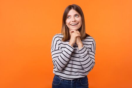 Portrait of adorable dreamy young woman with brown hair in long sleeve striped shirt standing, holding hands near face while dreaming, making wish. indoor studio shot isolated on orange background Фото со стока