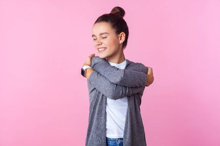 I love myself! Portrait of excited egoistic teenage girl with bun hairstyle in casual clothes embracing herself and smiling from pleasure, positive self-esteem. studio shot isolated on pink background Фото со стока