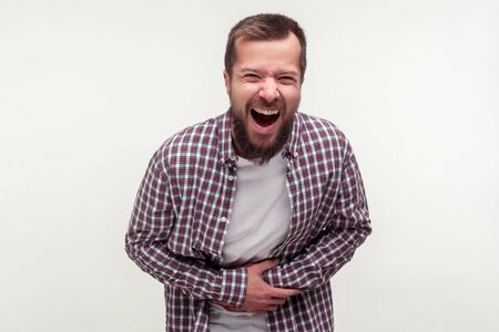 Porträt eines extrem aufgeregten, glücklichen, bärtigen Mannes in lässigem kariertem Hemd, der seinen Bauch hält und laut lacht, kichert und über einen amüsanten Witz kichert. Indoor-Studioaufnahme isoliert auf weißem Hintergrund