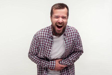 Portrait d'un homme barbu heureux extrêmement excité en chemise à carreaux décontractée tenant son ventre et riant fort, riant de rire à une blague amusante. Studio intérieur tourné isolé sur fond blanc