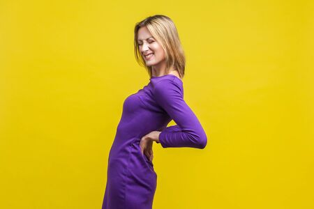 Backache. Portrait of young unhealthy woman in elegant tight purple dress standing with closed eyes, suffering lower back pain, kidney inflammation. indoor studio shot isolated on yellow background Фото со стока