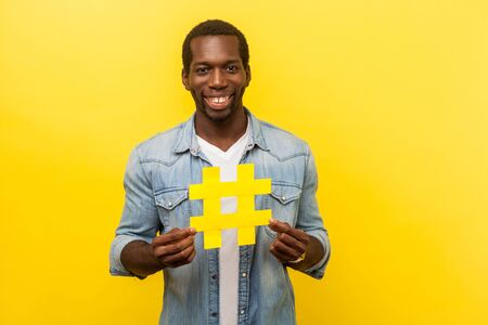 Viral hashtag. Portrait of positive man with attractive toothy smile in denim casual shirt holding large yellow hash symbol, popularity in social media. indoor studio shot isolated, yellow background