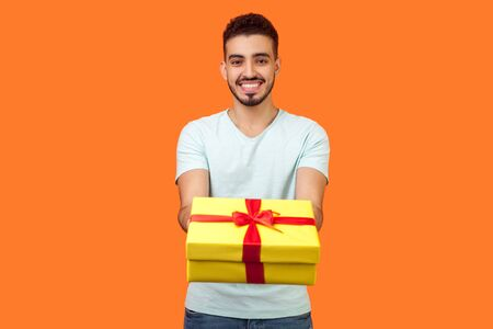 Portrait of happy generous brunette man with beard in white t-shirt smiling and giving gift box to camera, sharing holiday present, charity concept. indoor studio shot isolated on orange background