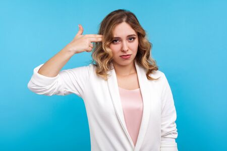 Portrait of frustrated woman with wavy hair in white jacket pointing finger gun to head with bored face expression, shooting herself in depression, tired of living. indoor studio shot, blue background