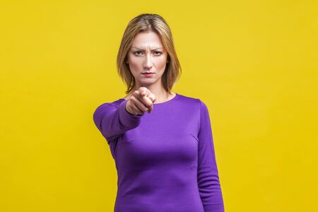 Hey you! Portrait of serious bossy woman in tight purple dress pointing at camera frowning with displeased angry face, saying you are guilty. indoor studio shot isolated on yellow background