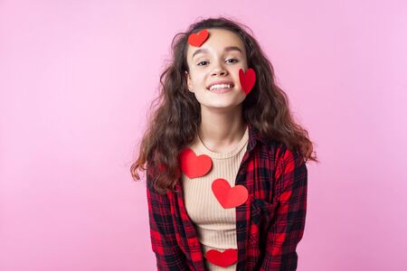 Valentines Day. Portrait of excited lovely teen girl with curly brunette hair and paper heart stickers on her face and clothes smiling happily at camera. indoor studio shot isolated on pink background