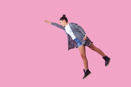 Portrait of cheerful ambitious brunette teenage girl with bun hairstyle in casual clothes flying with one raised hand, feeling super power. indoor studio shot isolated on pink background