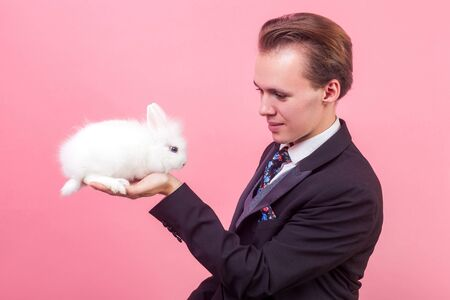 Pet adoption. Portrait of young positive man in elegant suit and with stylish hairdo looking at adorable white rabbit on his hand, domestic animal. indoor studio shot isolated on pink background