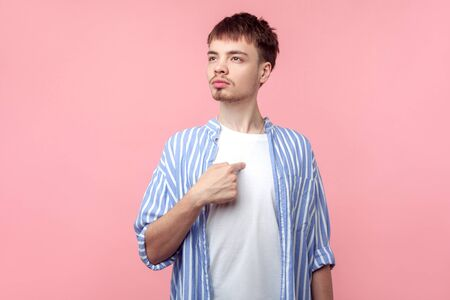 This is me! Portrait of young selfish brown-haired man with small beard and mustache in casual striped shirt pointing at himself, proud of achievements. indoor studio shot isolated on pink background
