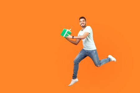 Full length portrait of excited joyous brunette man in sneakers and denim outfit smiling at camera while flying or running in air with gift box, present. studio shot isolated on orange background Фото со стока