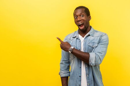 Wow, advertise here! Portrait of excited amazed man in denim casual shirt pointing left side with astonished expression, showing empty space for advertise. studio shot isolated on yellow background