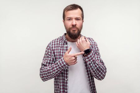 Look at the time! Portrait of serious bearded man in casual plaid shirt standing pointing at wristwatch meaning time to go, late hour, deadline at work. indoor studio shot isolated on white background