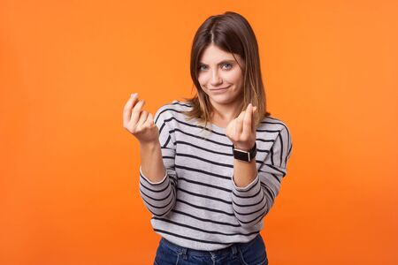 Portrait of smart beautiful woman with brown hair in long sleeve striped shirt standing showing money gesture with fingers, looking cunning at camera. indoor studio shot isolated on orange background