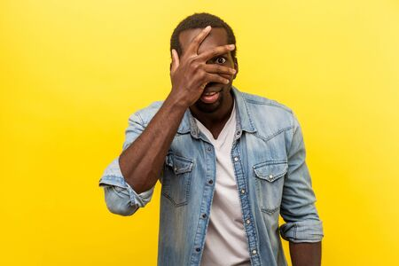 Portrait of positive interested man in denim casual shirt covering face and eyes with hand, peeking through fingers with happy curious expression. indoor studio shot isolated on yellow background