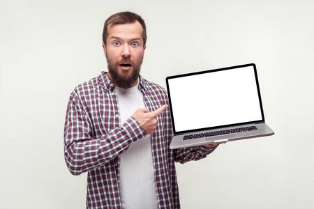Portrait of shocked bearded man in casual plaid shirt holding laptop and pointing at empty screen, surprised about computer application, internet news. indoor studio shot isolated on white background Фото со стока