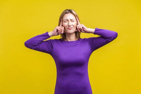 Intense headache. Portrait of upset sick woman in elegant tight purple dress standing touching her temples and grimacing from pain, suffering migraine. indoor studio shot isolated on yellow background Фото со стока