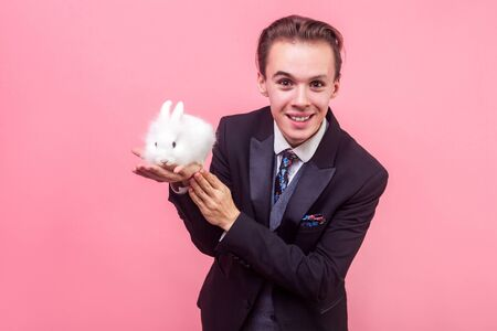 Pet care. Portrait of cheerful handsome man in elegant suit and with stylish hairdo standing holding cute bunny rabbit on his palm, smiling at camera. indoor studio shot isolated on pink background