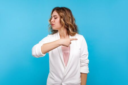 Get out! Portrait of mad bossy woman with wavy hair in white jacket pointing to the side and turning away with angry vexed face, giving order to leave. indoor studio shot isolated on blue background