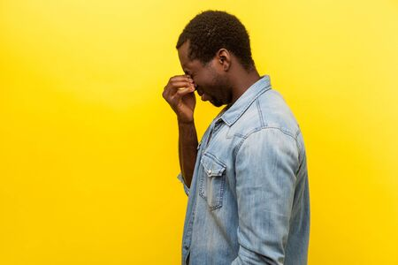 Side view portrait of distressed man with bristle in denim casual shirt standing with closed eyes crying hard, desperate and worried about problem. indoor studio shot isolated on yellow background