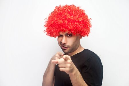 Hey you, beauty! Portrait of funny positive man with bristle and red wig pointing to camera and winking playfully, flirting and getting acquaintance, asking for a date. studio shot, white background