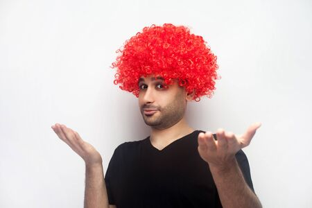 Dont know, who cares. Portrait of funny bizarre man with bristle and curly red wig raising hands in bewilderment, looking with indignant confused expression. studio shot isolated on white background