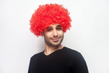 Portrait of funny stylish hipster man with bristle and curly red wig on his head smiling at camera, looking playful positive, optimistic lifestyle. indoor studio shot isolated on white background