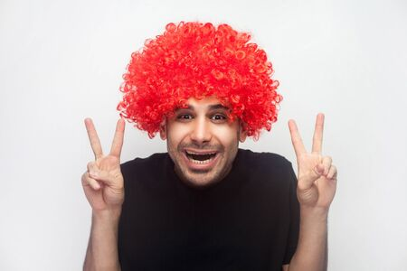 Portrait of friendly hipster man with bristle and curly red wig showing double v sign, victory or peace hand gesture and hesitantly funny shy smiling. indoor studio shot isolated on white background Фото со стока