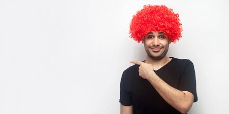 Look here! Portrait of stylish funny happy man with red wig smiling and pointing to the side, showing empty copy space for advertisement, freespace. indoor studio shot isolated on white background