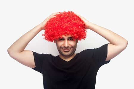 Portrait of crazy hipster, joyful man with bristle and in t-shirt touching red wig on his head and smiling at camera, looking funny with bright hair. indoor studio shot isolated on white background