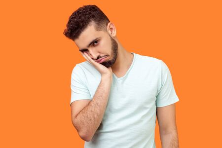 I'm bored, tired of everything. Portrait of brunette man with beard in white t-shirt looking at camera with disinterest, dull tedious facial expression. indoor studio shot isolated, orange background