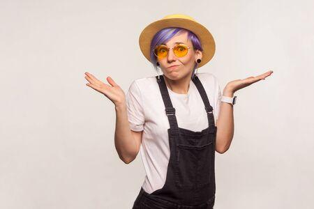 Ni idea. Retrato de chica inconformista de glamour confusa despistada con cabello violeta con gafas de sol y sombrero encogiéndose de hombros, no sabe la respuesta, expresión de desconcierto incierta. fondo blanco, tiro del estudio