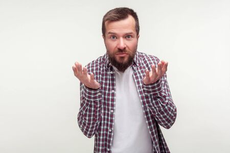How could you! Portrait of upset bearded man in casual plaid shirt raising hands looking confused disgruntled at camera, waiting for explanation. indoor studio shot isolated on white background Banco de Imagens