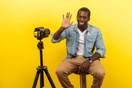 Portrait of cheerful friendly happy man in denim casual clothes smiling at his professional dslr camera, waving hand saying hello when starting video. indoor studio shot