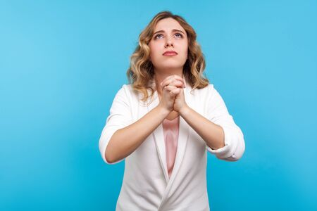 Please, I'm begging! Portrait of frustrated woman with wavy hair in white jacket looking up with imploring look, holding hands in prayer and asking, pleading. studio shot isolated on blue background