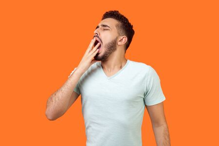 I need rest. Portrait of sleepy brunette man with beard in casual white t-shirt yawning and covering mouth with hand, feeling exhausted, lack of sleep. indoor studio shot isolated on orange background