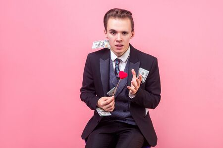 Portrait of unhappy rich businessman in expensive suit with lots of dollars in pockets holding toy heart and gesturing with hand do you really love me. indoor studio shot isolated on pink background Imagens