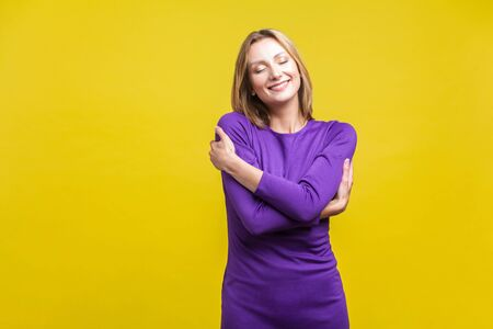 I love myself. Portrait of satisfied selfish woman in elegant tight purple dress embracing herself, standing with closed eyes smiling from pleasure. indoor studio shot isolated on yellow background Stock Photo