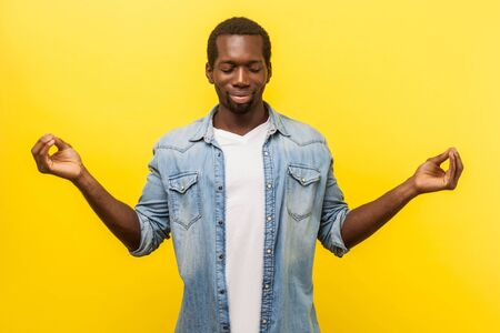 Balance and harmony. Portrait of peaceful positive man in denim casual shirt with rolled up sleeves holding fingers in mudra gesture, meditating with closed eyes. indoor studio shot isolated on yellow Stock Photo