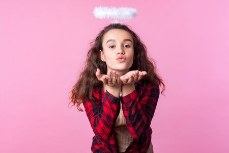 Portrait of lovely teenage girl with curly brunette hair in plaid shirt and toy halo above head sending air kiss with pouted lips, romance on valentines day. studio shot isolated on pink background