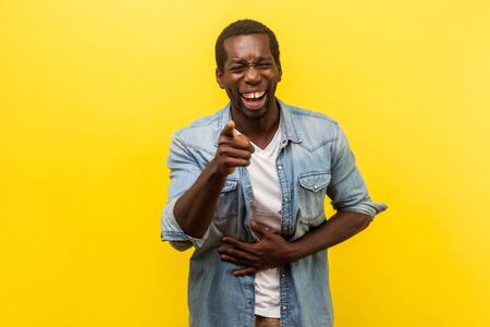 Portrait of joyful positive man in denim shirt with rolled up sleeves holding hand on belly and laughing out loud, pointing at camera, mocking you. indoor studio shot isolated on yellow background