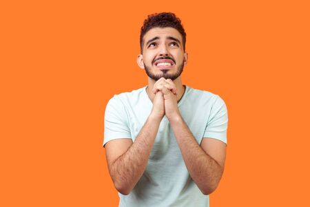 Please, I need help! Portrait of worried brunette man with beard in white t-shirt holding arms in prayer, looking up and pleading with hopeful eyes. indoor studio shot isolated on orange background