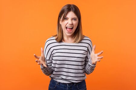 Portrait of angry, crazy young woman with brown hair in long sleeve shirt standing with raised arms and open mouth, full of rage shouting at camera. indoor studio shot isolated on orange background Stock fotó
